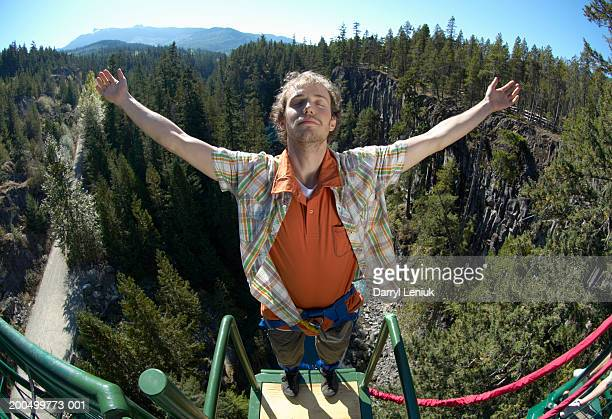 Young man standing on bungee jump platform, (wide angle)