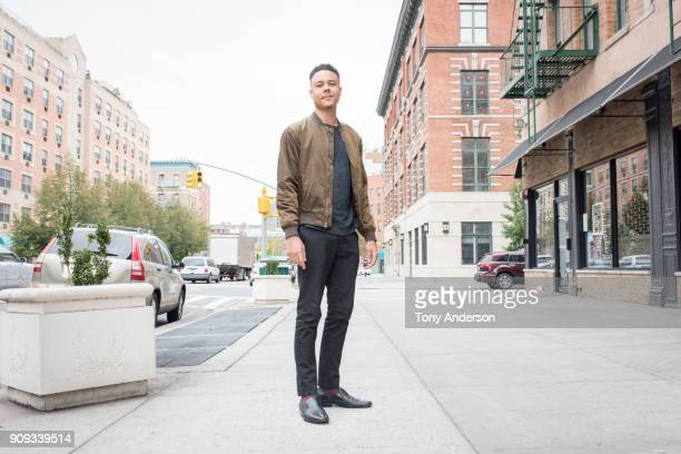 young man standing on city sidewalk - standing photos et images de collection