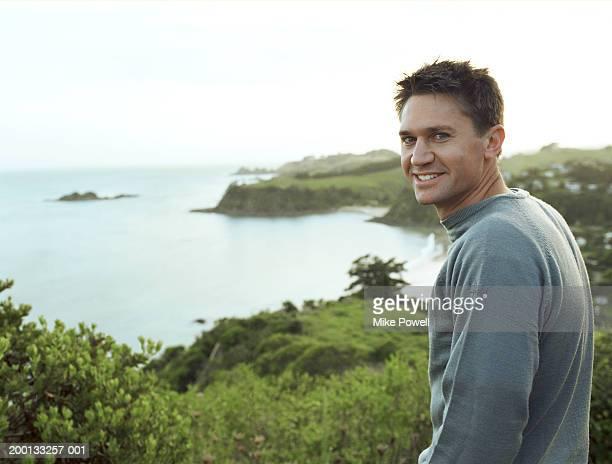 Young man standing on cliff overlooking coastline