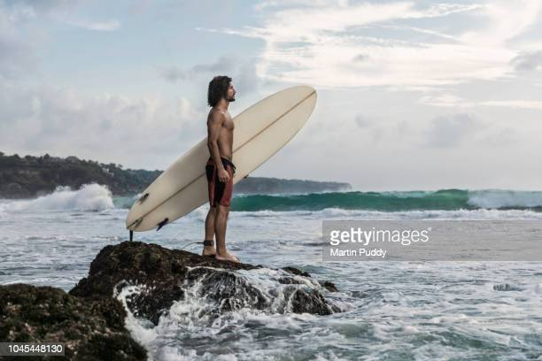 young man standing on coastline, holding a surfboard