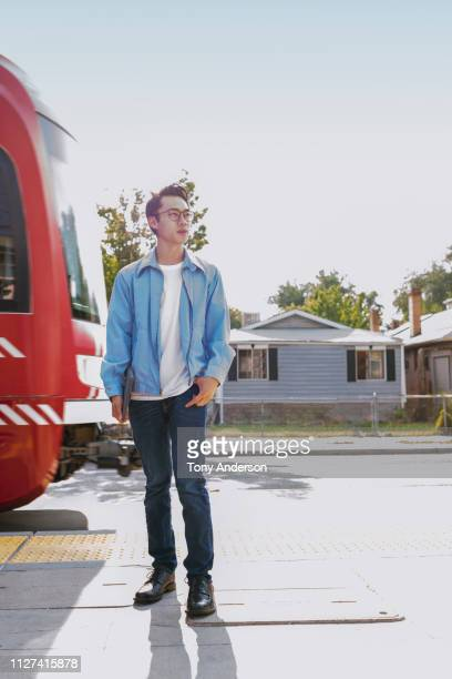 young man standing on commuter train platform - ジャケット ストックフォトと画像