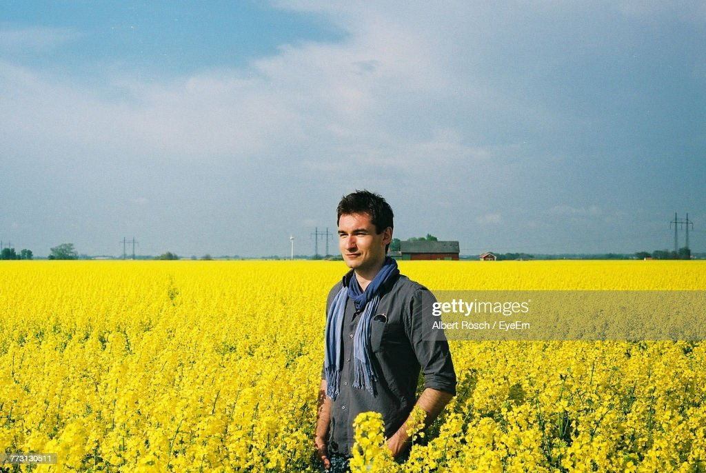 Young Man Standing On Field Against Cloudy Sky : Photo