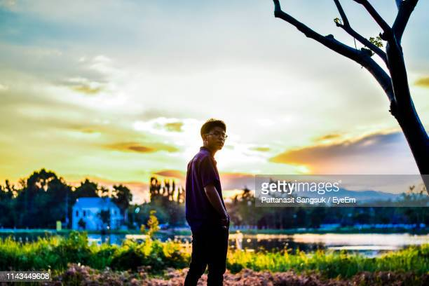 young man standing on field against sky during sunset - pattanasit stock pictures, royalty-free photos & images