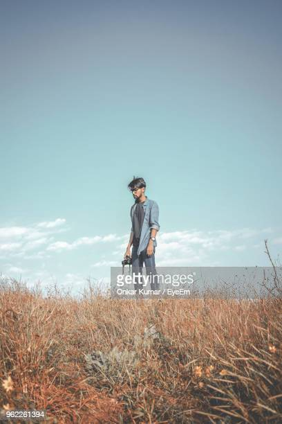 Young Man Standing On Field Against Sky