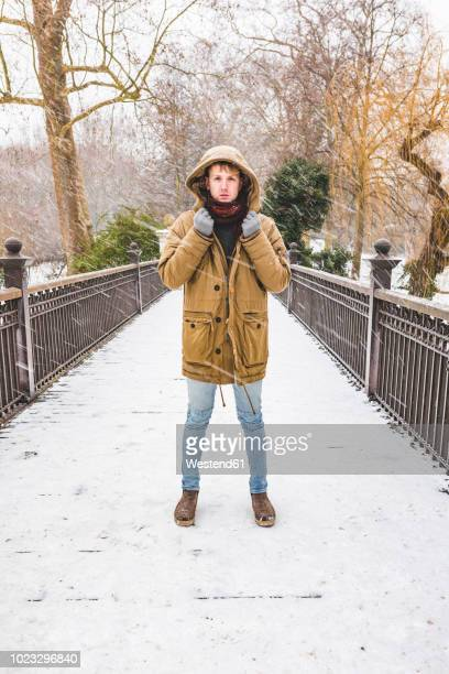 young man standing on footbridge in a park on a snowy day - winter coat stock pictures, royalty-free photos & images