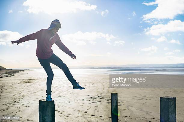 Young man standing on groynes, Brean Sands, Somerset, England