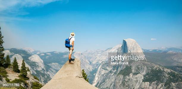 young man standing on ledge, looking at the half dome, view from glacier point, yosemite national park, california, usa - yosemite valley stock photos and pictures