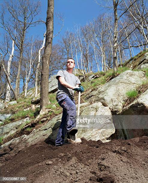 Young man standing on mound of earth resting foot on spade