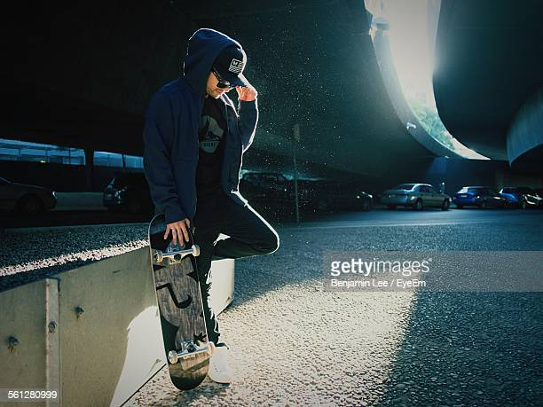 Young Man Standing On One Leg With Skateboard Under Bridge
