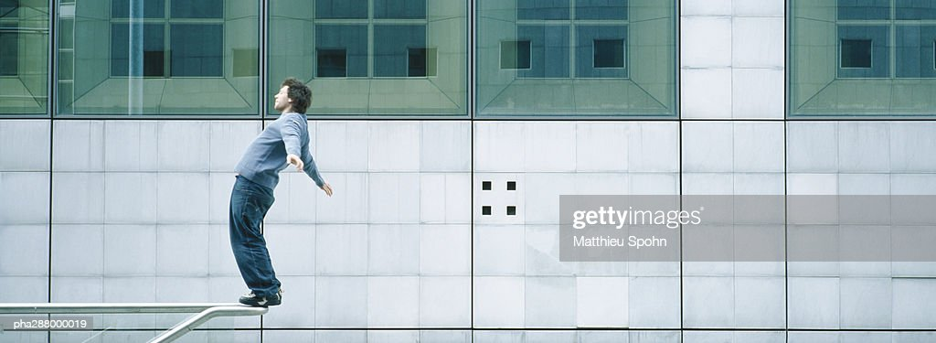 Young man standing on rail : Stock Photo
