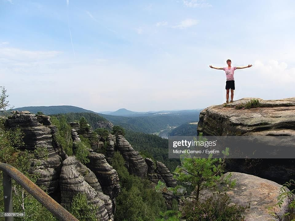 Young Man Standing On Rock In Mountains : Foto stock