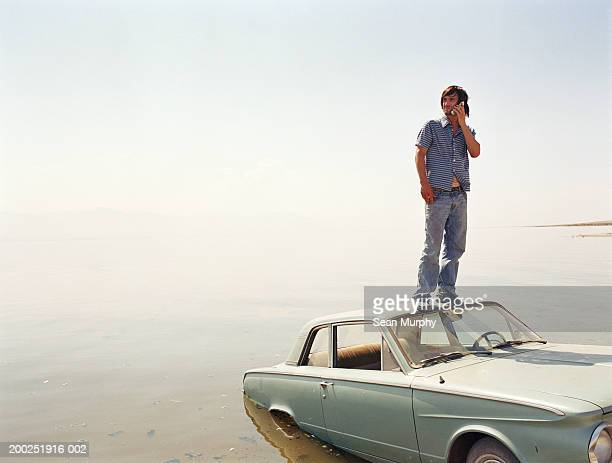 Young man standing on roof of car in water, using mobile phone