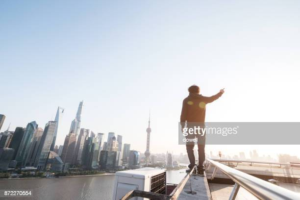 young man standing on roof of modern building with sunbeam
