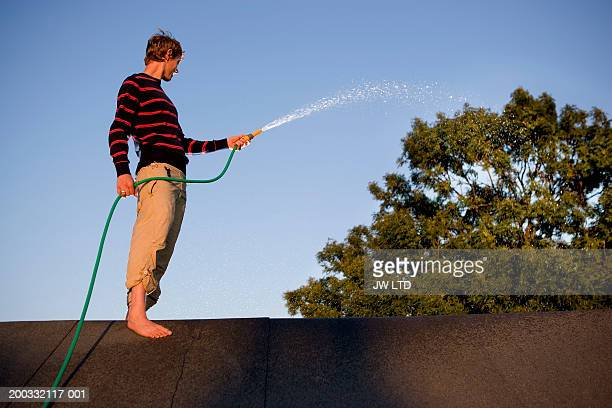 Young man standing on rooftop spraying hose, side view