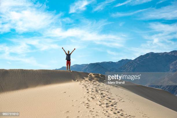 Young man standing on sand dune, Mesquite Flat Sand Dunes, Death Valley, Death Valley National Park, California, USA
