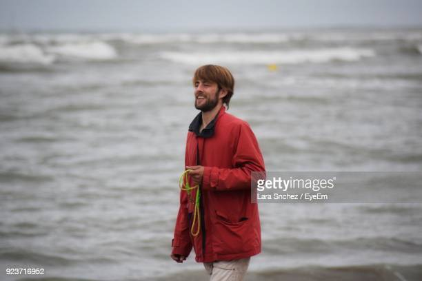 Young Man Standing On Shore At Beach