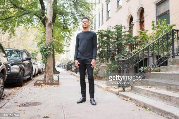 Young man standing on sidwalk in his city neighborhood