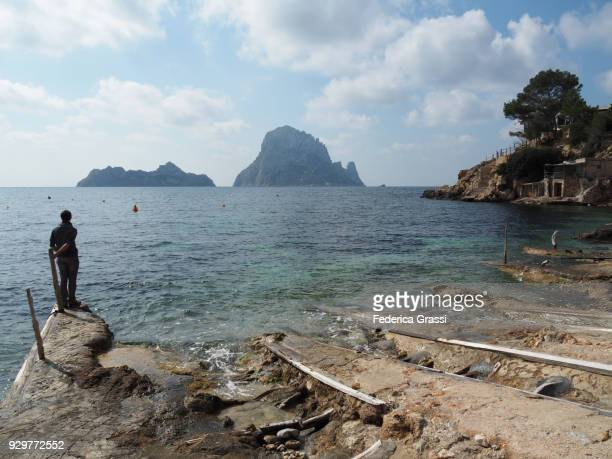 Young Man Standing On Small Jetty At Cala d'Hort, Ibiza