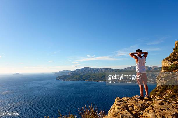 young man standing on steep cliff at the cote d'azur - cassis stock pictures, royalty-free photos & images