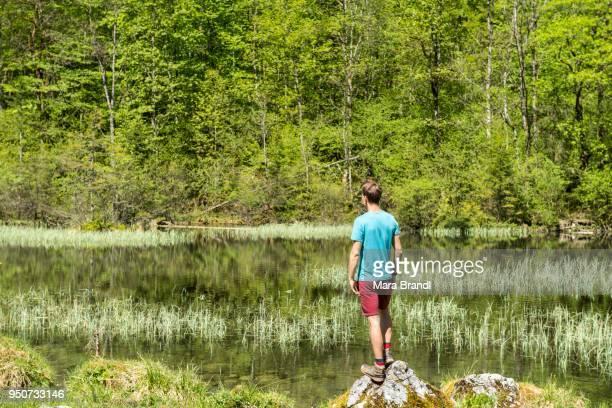 Young man standing on stone at lake, Mittersee, Salet am Koenigssee, National Park Berchtesgaden, Berchtesgadener Land, Upper Bavaria, Bavaria, Germany