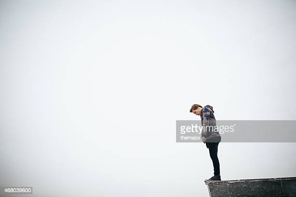 young man standing on stone block - suicide stock photos and pictures