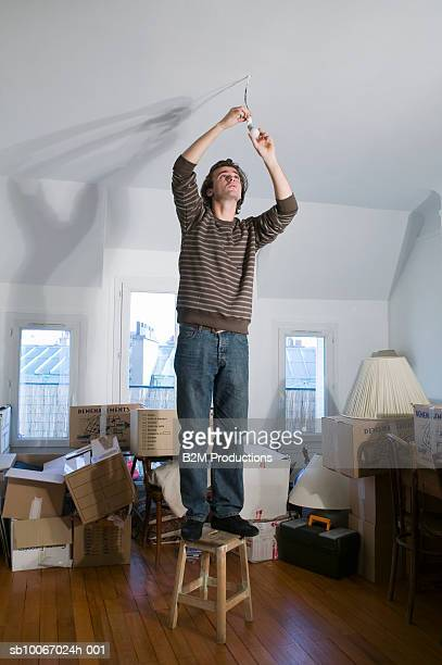 Young man standing on stool, fixing light bulb