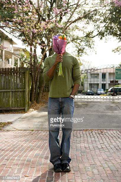 Young man standing on street covering his face with bouquet of flowers