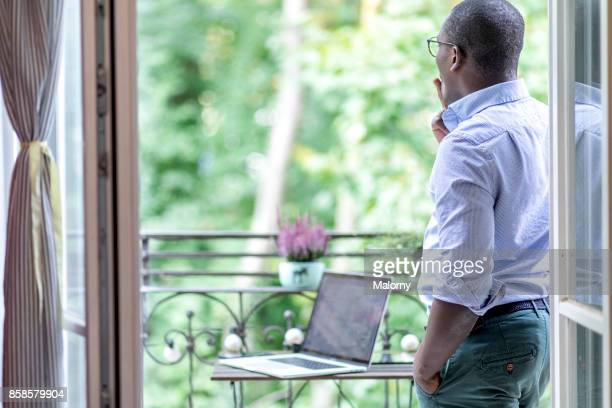 Young man standing on the balcony, smoking, taking a break from work. Home office.