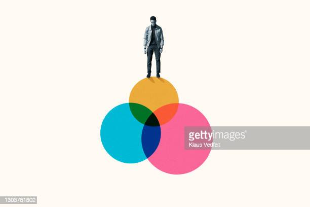 young man standing on top venn diagram of colorful circles - infographics stock pictures, royalty-free photos & images