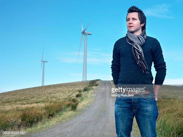 Young man standing on track, wind turbines in background