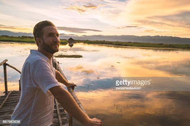 Young man standing on wooden lake pier contemplates sunrise, Myanmar