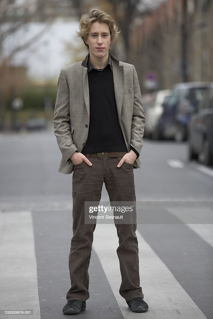 Young man standing on zebra crossing, hands in pockets, portrait : Stock Photo