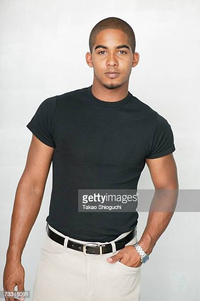 young man standing, one hand in pocket, portrait - zwart shirt stockfoto's en -beelden