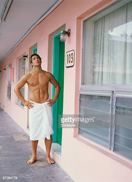 Young man standing outside motel room, wearing nothing but a towel
