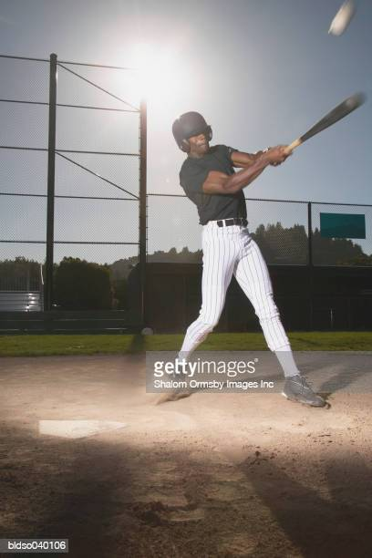 Young man standing swinging a baseball bat