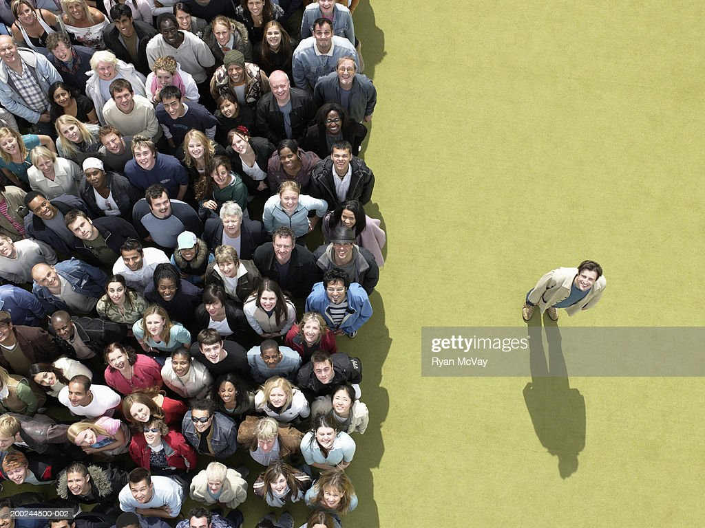 Young man standing to side of large crowd looking up, overhead view : Stock Photo