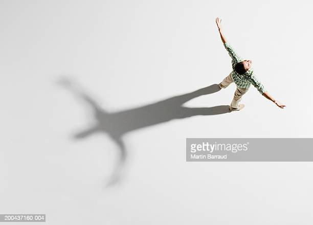 young man standing with arms outstretched, overhead view - arms outstretched stock pictures, royalty-free photos & images