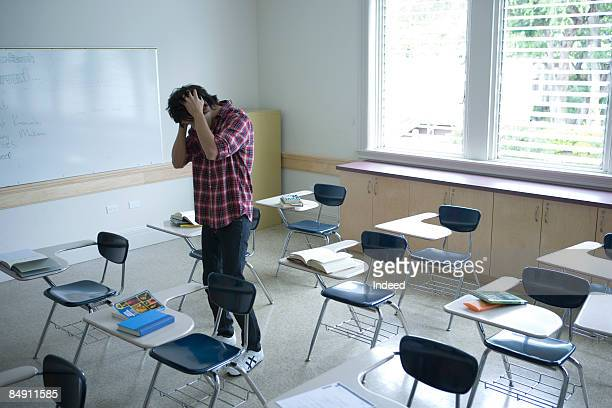 Young man standing with hands on head in classroom