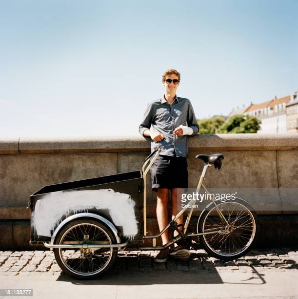 young man standing with his bike in city area - broken arm stock pictures, royalty-free photos & images