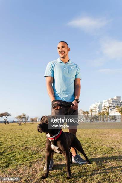 Young man standing with his pit bull terrier at the park.