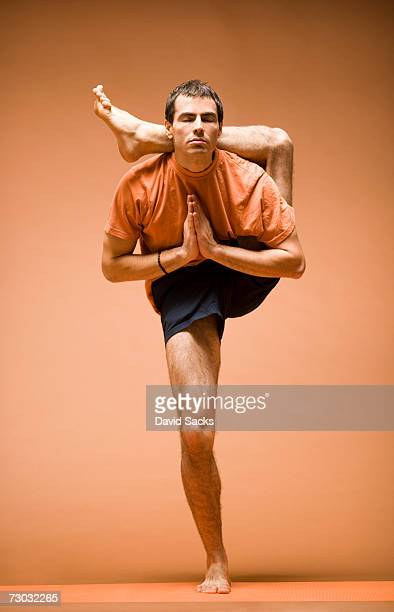 Young man standing with leg behind head in yoga pose, front view