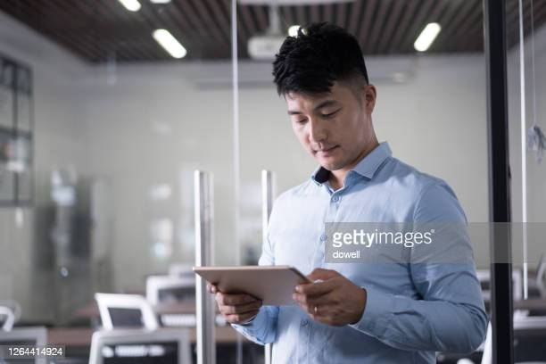 young man stands and uses digital tablet n modern office - 電子 ストックフォトと画像
