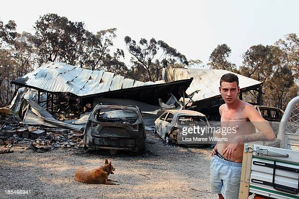 A young man stands in front of a family home business destroyed by bushfire as seen on October 21 2013 in Yellow Rock Australia One man has died and...