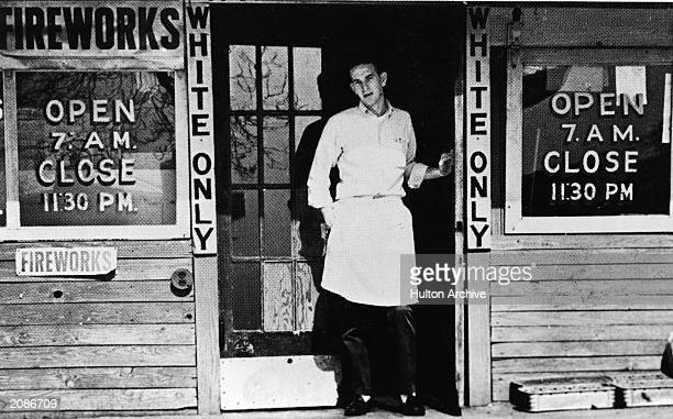 A young man stands in the doorway of a store marked 'White Only ' circa 1950