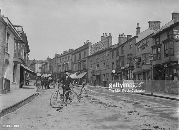 Young man stands in the middle of quiet road holding onto two bicycles as a horse and cart approaches from behind the Blackwells Angel hotel two...