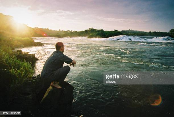 junger mann starrt auf die quelle des nils - süßwasser stock-fotos und bilder