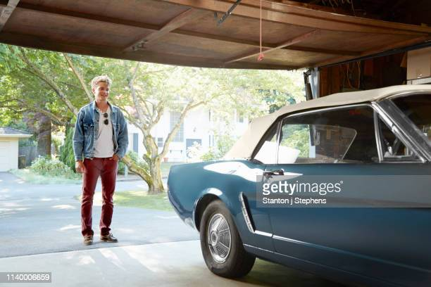 young man staring into garage at vintage car - garage stock pictures, royalty-free photos & images