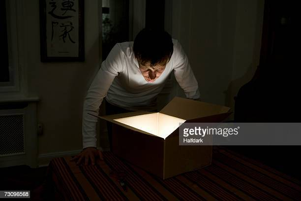 Young man staring into illuminated cardboard box