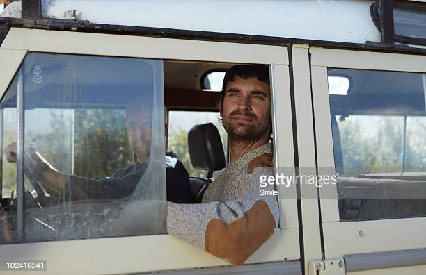 Young man staring out of 4x4 vehicle window