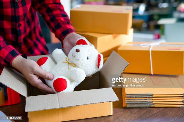 a young man starts a small business owner packing a teddy bear in a box at work. independent male seller prepares products for the packing process at home online sales internet marketing e-commerce concept - e mail stockfoto's en -beelden